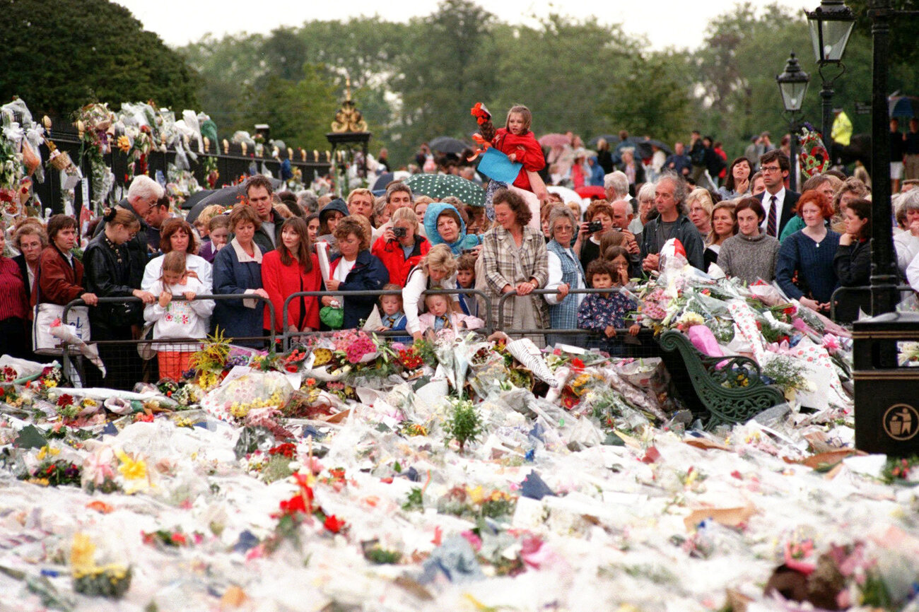 Thousands of mourners gather on Sept. 3, 1997, to lay flowers and cards atop the immense mound of flowers at the gates of Kensington Palace in London, the official residence of Diana, Princess of Wales. (Rick Bowmer/AP)
