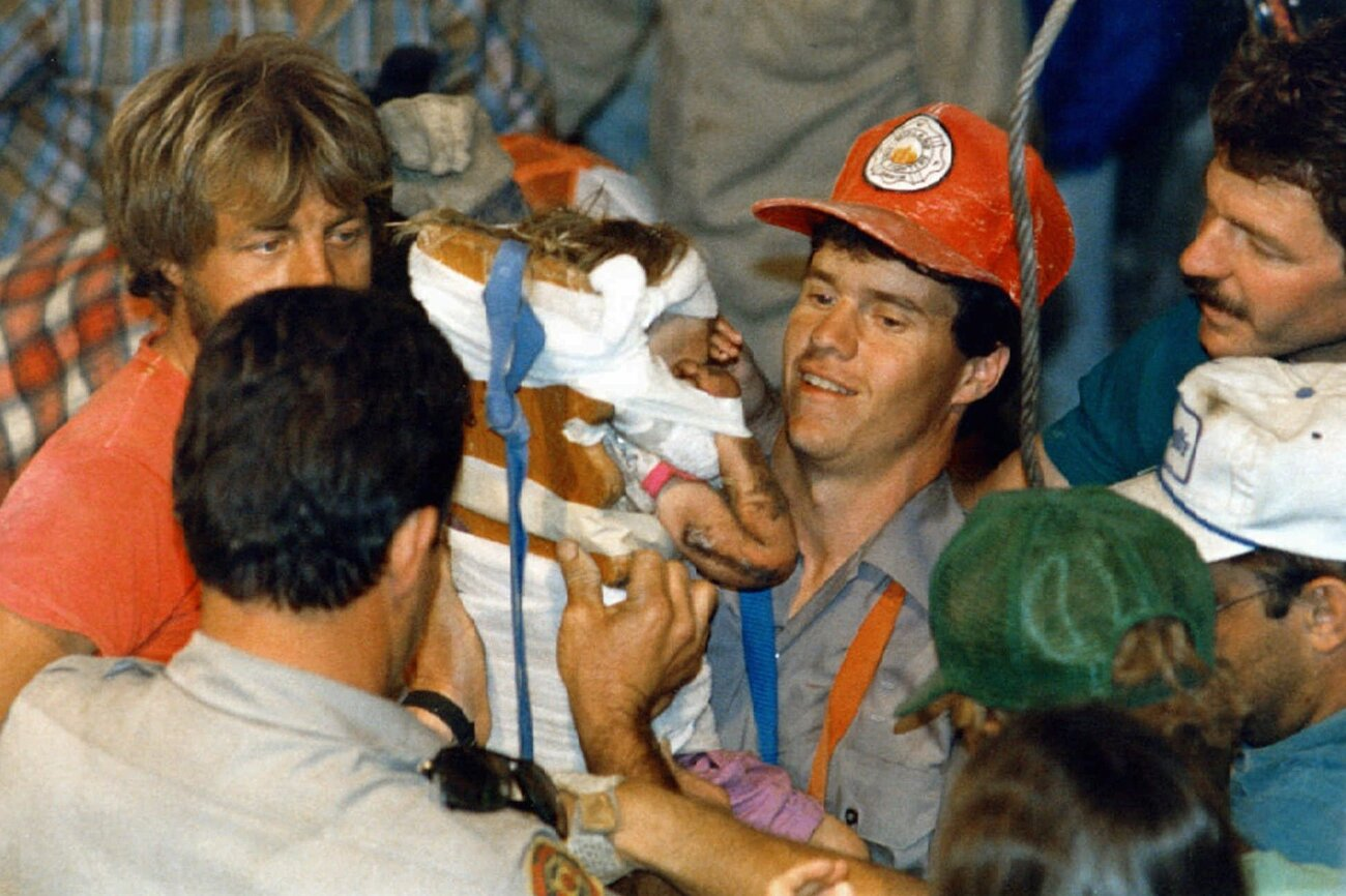 Rescue worker Steven Forbes carries 18-month-old Jessica McClure on Oct. 16, 1987, shortly after she was rescued from an abandoned water well in Midland, Texas. (Eric Gay/AP)