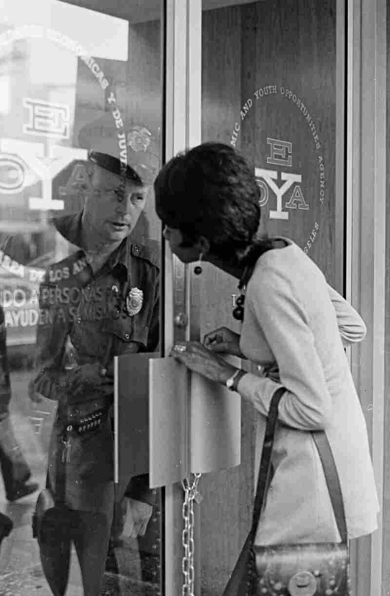 A woman outside the locked Economic and Youth Opportunities Agency exchanges glances with a police officer inside. Circa 1973.