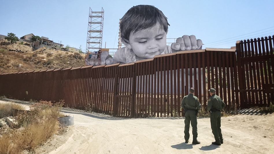 As Boy Peers Curiously Over Border Wall His Artist Asks