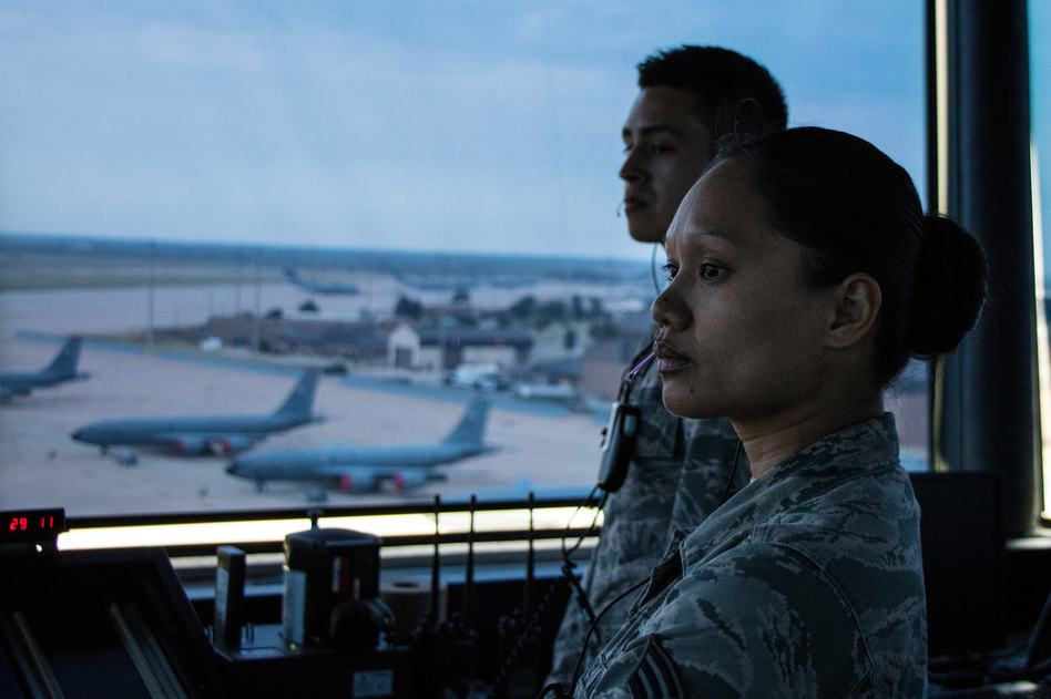 Senior Airman Yazmine Nanasca with a control tower crew at Altus Air Force Base guide a C-17 cargo plane a KC-135 tanker as it taxis to the runway for a day-long training mission in southwestern Oklahoma. (Joe Wertz/StateImpact Oklahoma)