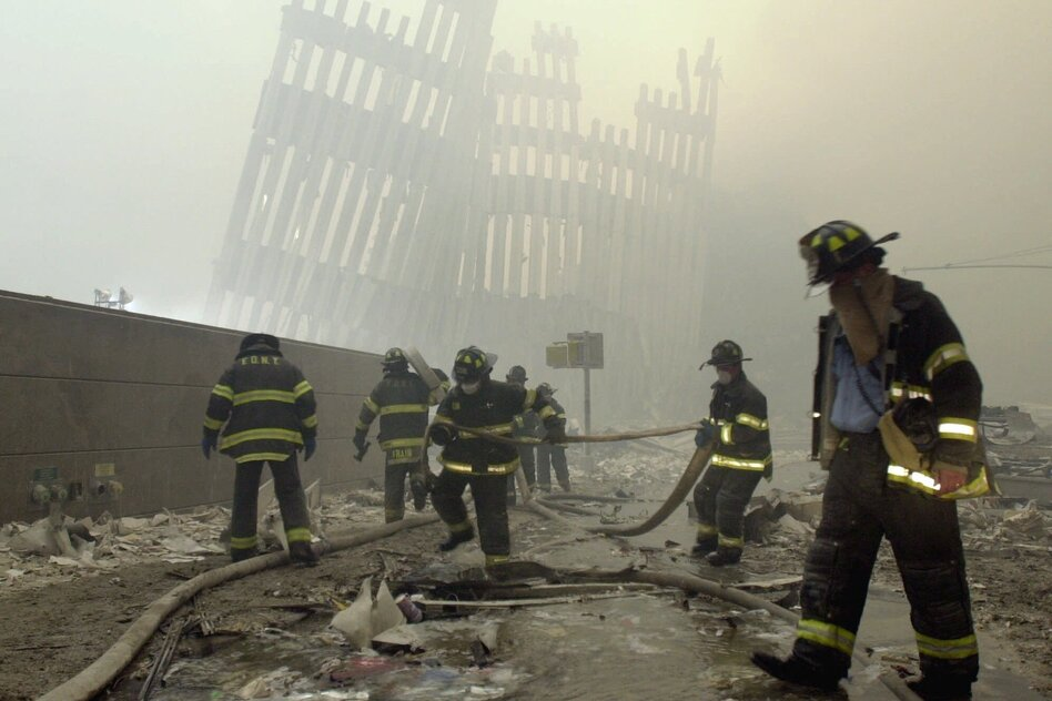Firefighters work beneath the vertical struts of the World Trade Center's twin towers, in Lower Manhattan, following the attacks of Sept. 11, 2001. (Mark Lennihan/Associated Press)