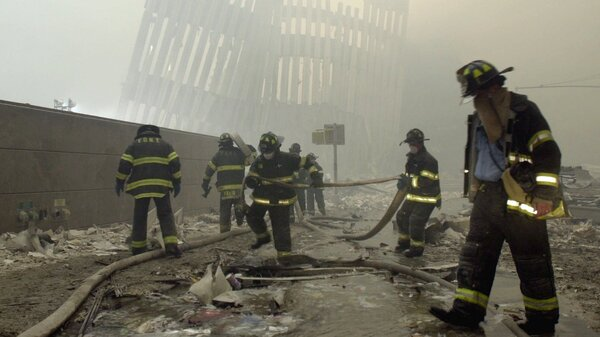 Firefighters work beneath the vertical struts of the World Trade Center