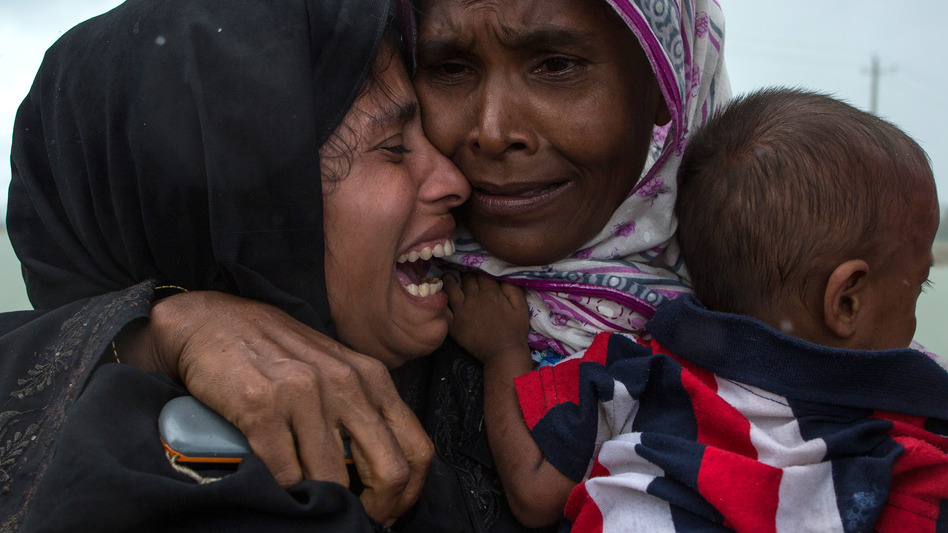 Rohingya refugees embrace one another, finally reunited after a perilous journey by boat from Myanmar to Bangladesh. (Dan Kitwood/Getty Images)