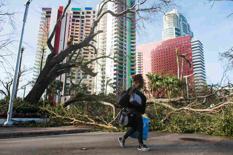 Estrella Palacios walks through debris caused by Hurricane Irma in Miami. While the full extent of Irma's damage isn't yet known, the storm has weakened at a faster rate than expected.