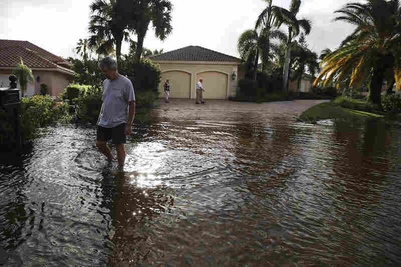 People inspect their neighborhood that was flooded by Hurricane Irma in Bonita Springs, Fla. On Sunday, Hurricane Irma hit Florida's west coast, leaving widespread damage and flooding.