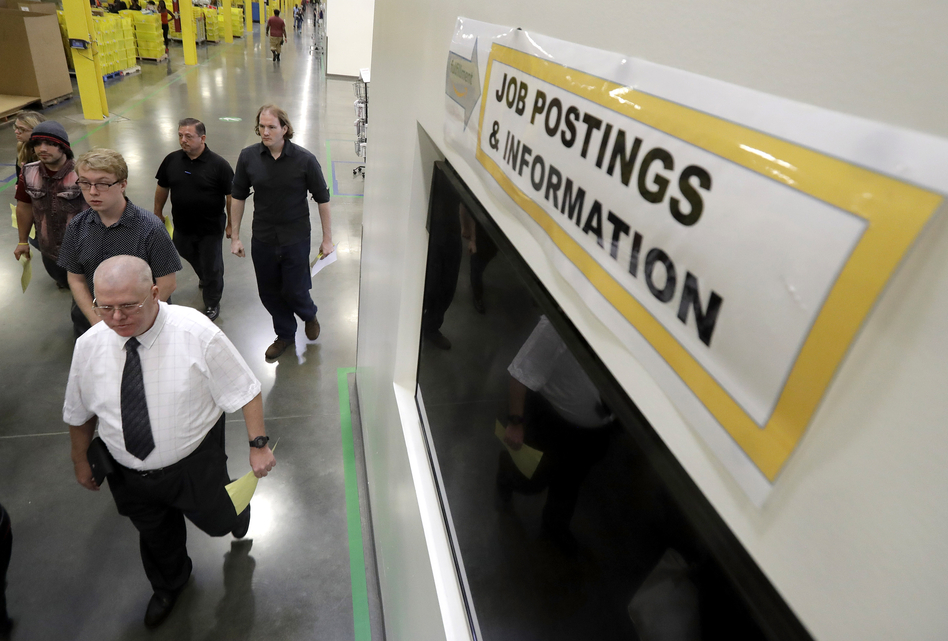 Job candidates take a tour of the Amazon fulfillment center in Robbinsville, N.J., during a job fair last month. The Census Bureau says increased employment is what's driving higher income numbers. (Julio Cortez/AP)