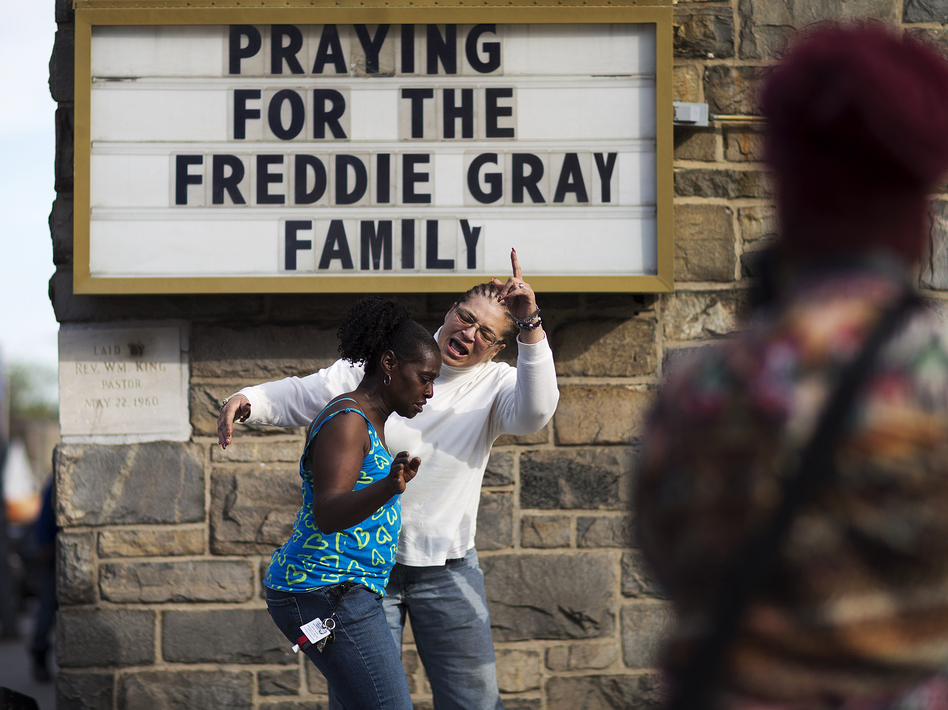 Women dance and pray to music over a loudspeaker outside a church following the funeral for Freddie Gray in 2015. (David Goldman/AP)