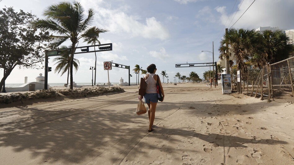 Hurricane Irma dumped water on towns and covered oceanside streets with sand in several states. Here, Amela Desanto walks on the sand-covered road along Fort Lauderdale Beach on Monday, as the storm headed inland. (Andrew Innerarity/For The Washington Post/Getty Images)