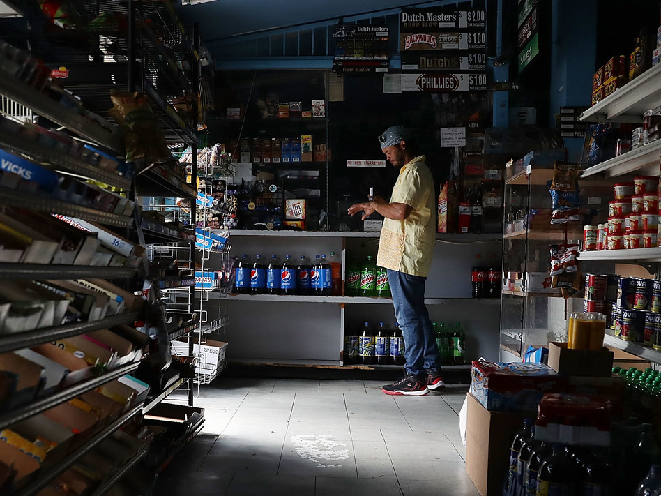A person visits a Miami store that doesn't have electricity on Tuesday. Much of Florida was without power two days after Hurricane Irma battered the state. (Joe Raedle/Getty Images)