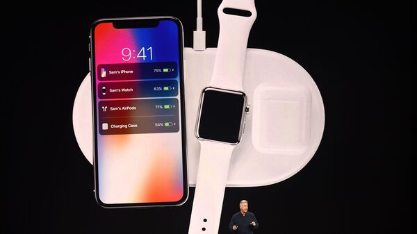 Apple executive Philip Schiller presents a wireless charging system, displayed with the new iPhone X and Apple Watch alongside cordless headphones called AirPods.