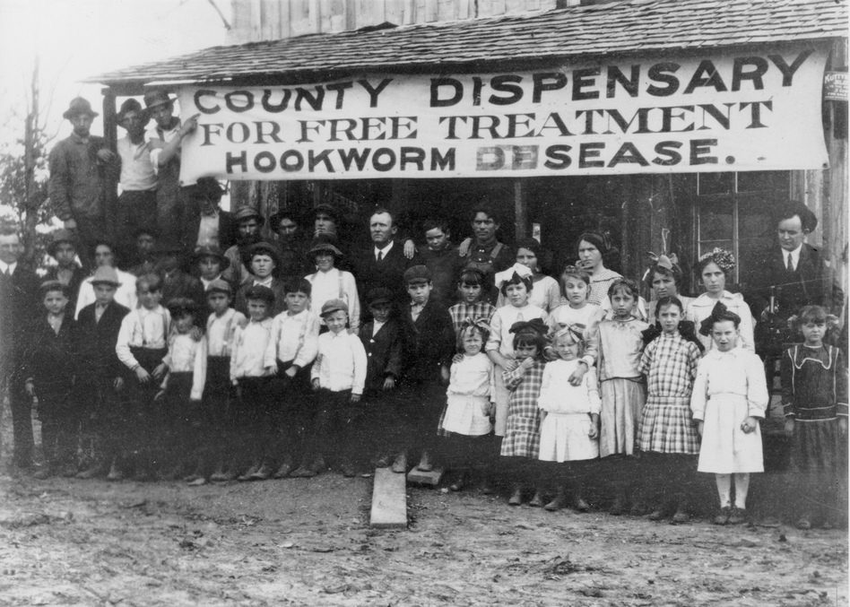 "Hookworm was a fact of American life a century ago. In this photo, circa 1912, from Faulkner County, Arkansas, resident gather outside a ""dispensary"" for free treatment."