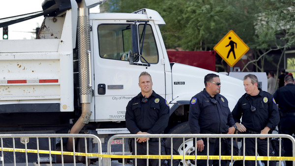 Phoenix police officers stand beside a dump truck blocking a road outside the Phoenix Convention Center on Aug. 22. Protests were held against President Donald Trump as he planned to host a rally inside the convention center.