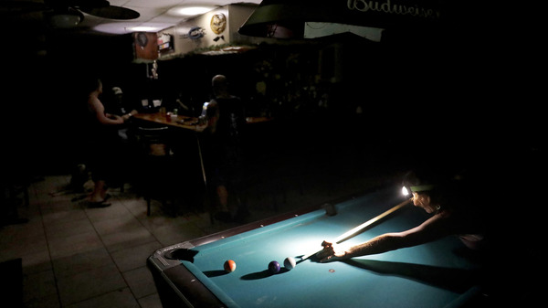 Playing pool during a power outage from Hurricane Irma, Lisa Borruso used a headlamp to line up a shot at Gators