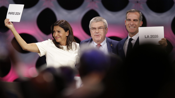 Paris and Los Angeles have been awarded the honor of hosting the 2024 and 2028 Olympic games, respectively. Pictured above: IOC President Thomas Bach (center), Paris Mayor Anne Hidalgo (left), and Los Angeles Mayor Eric Garrett.