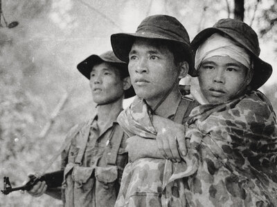 Burns explores the Vietnam War from multiple perspectives in his new documentary. Here, a Viet Cong guerrilla fighter carries a wounded friend during action along the Cambodian border. (PBS)