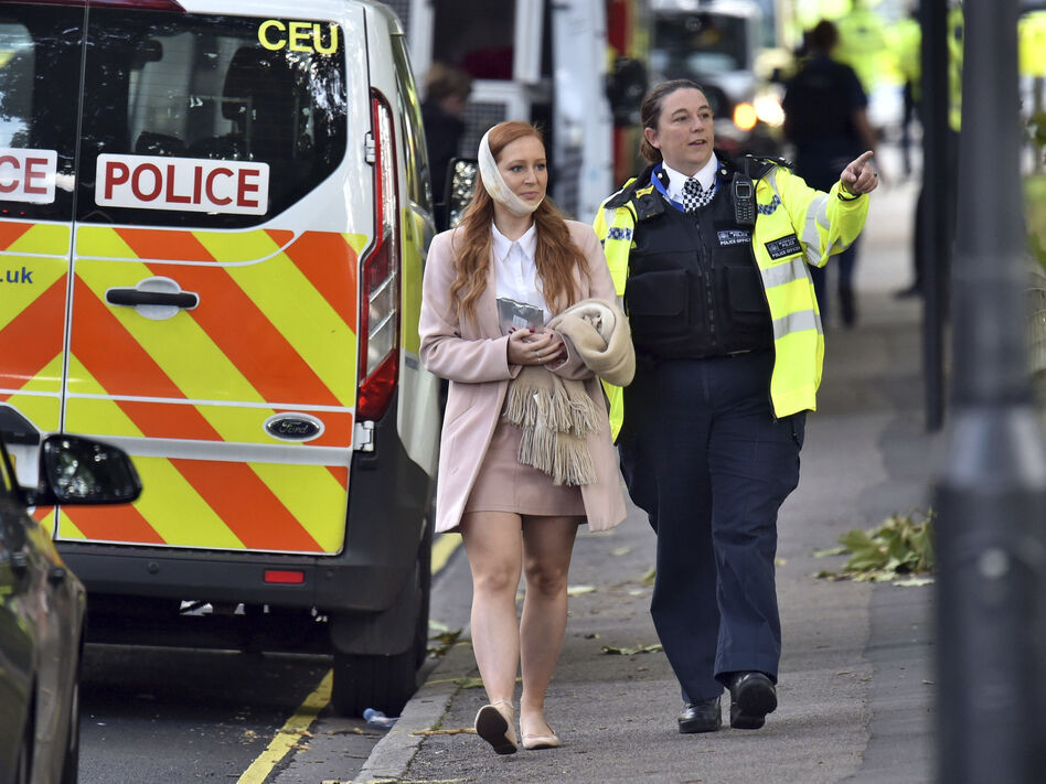 An injured woman is assisted by a police officer close to Parsons Green station in west London after Friday's explosion on a packed subway train was declared a terrorist incident. (Dominic Lipinski/AP)