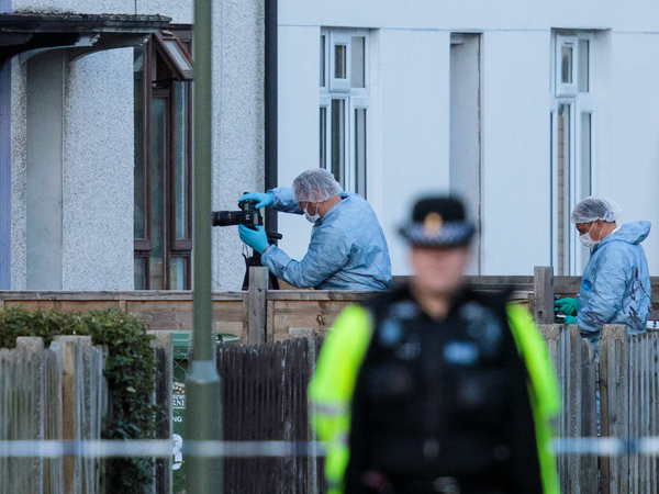 """Forensics officers investigate a property in relation to Friday's terror attack in London. The threat level in the United Kingdom was raised to """"critical"""" after the attack, but it was lowered to """"severe"""" on Sunday."""