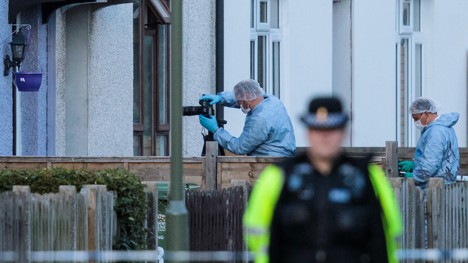 "Forensics officers investigate a property in relation to Friday's terror attack in London. The threat level in the United Kingdom was raised to ""critical"" after the attack, but it was lowered to ""severe"" on Sunday."