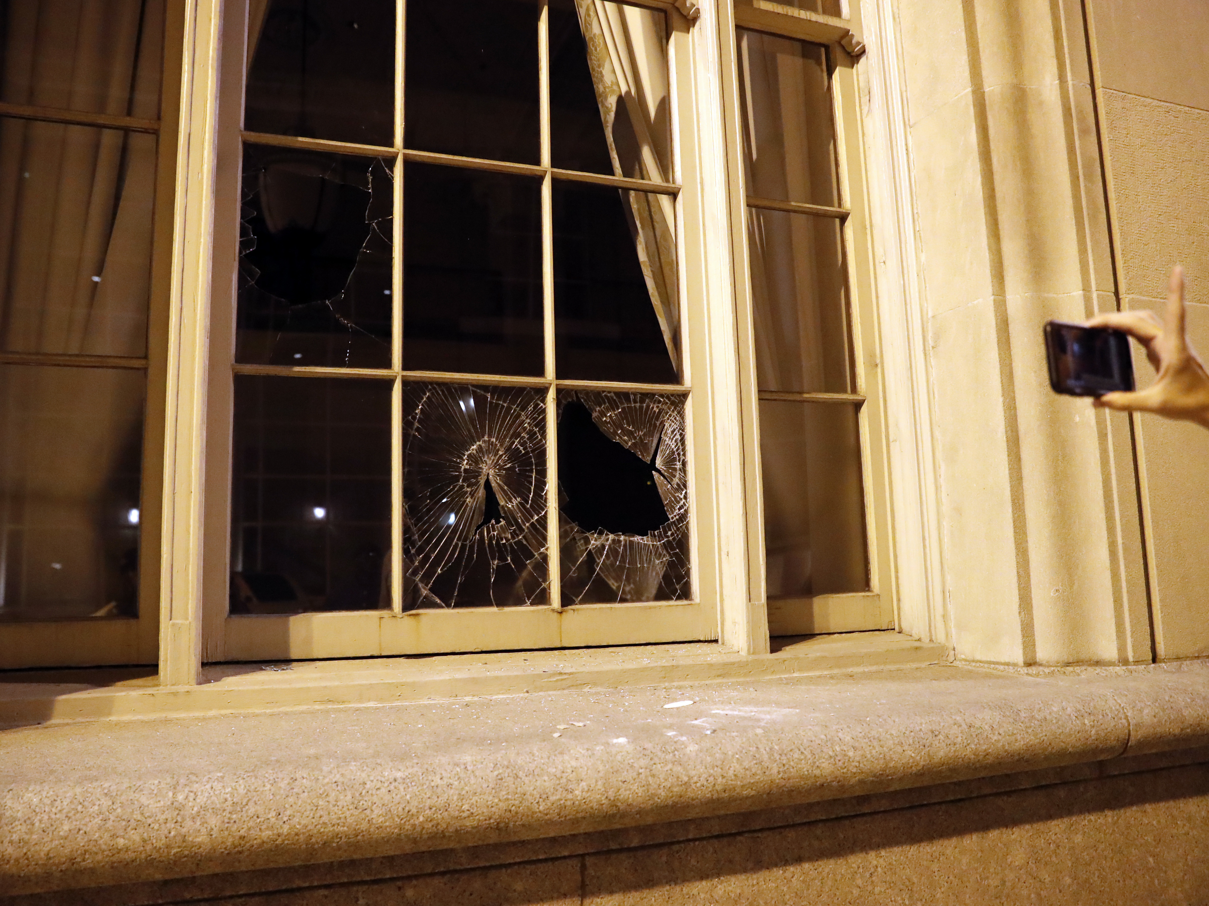 A person takes a photo of a broken window after protests Sunday in St. Louis. (Jeff Roberson/AP)