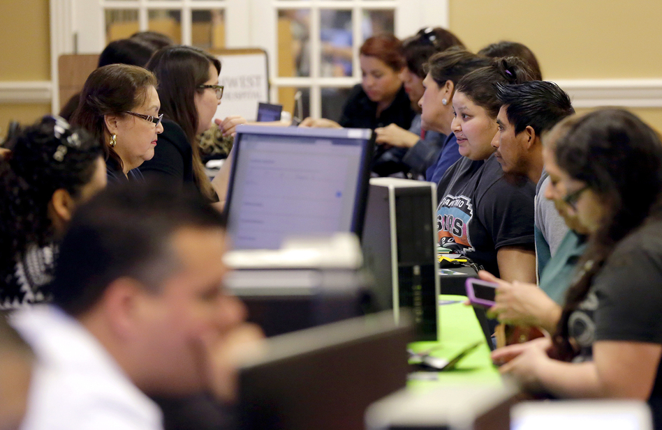 Affordable Care Act navigators helped guide those looking for insurance during an enrollment event at San Antonio's Southwest General Hospital last year. Beyond helping with initial enrollment, navigators often follow up with help later, as an applicant's income or job status changes. (Eric Gay/AP)