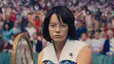 A Competitor And A Clown Walk Onto A Tennis Court In 'Battle Of The Sexes'