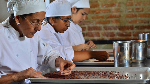 Entrepreneurs sort cocoa beans on a tray at Cacao de Origen, a school founded by Maria Di Giacobbe to train Venezuelan women in the making of premium chocolate. Zeina Alvarado (left) later found work in a bean-to-bar production facility in Mexico.