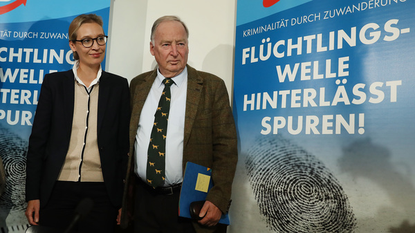 "Alice Weidel and Alexander Gauland, leading candidates of the right-wing, populist Alternative for Germany (AfD) political party, stand near an AfD poster that reads: ""Crime Through Immigration, The Refugee Wave Leaves Behind Clues!"" Sept. 18 in Berlin."