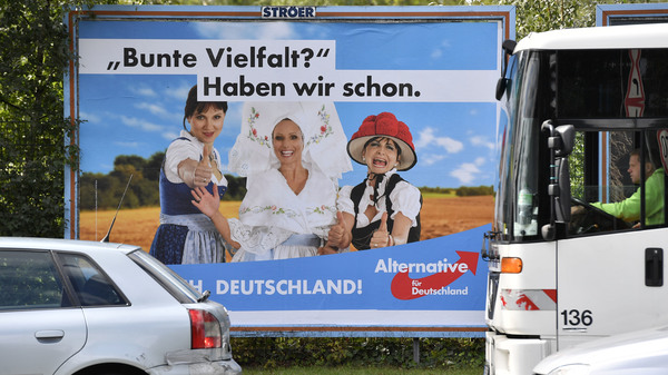 """A poster in Essen showing women in traditional German dress promotes the far-right party Alternative for Germany. The poster says, """"Colorful variety? We have already."""""""