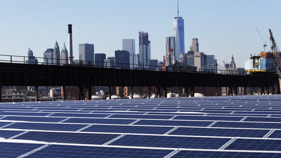 U.S. regulators say cheap solar panels from China have hurt U.S. manufacturers. Here, the Manhattan skyline is seen beyond a rooftop covered with solar panels. (Mark Lennihan/AP)