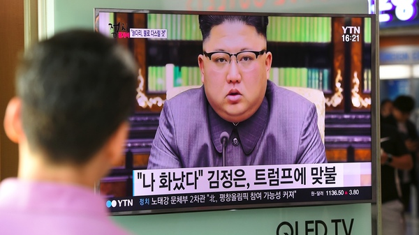 A man at a railway station in Seoul watches a television news screen showing North Korean leader Kim Jong Un delivering a statement in Pyongyang.