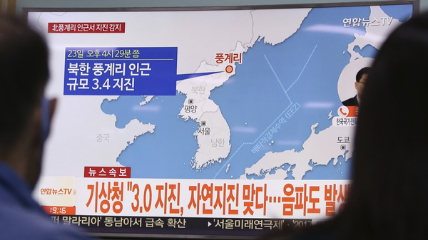People watch a TV news program reporting North Korea