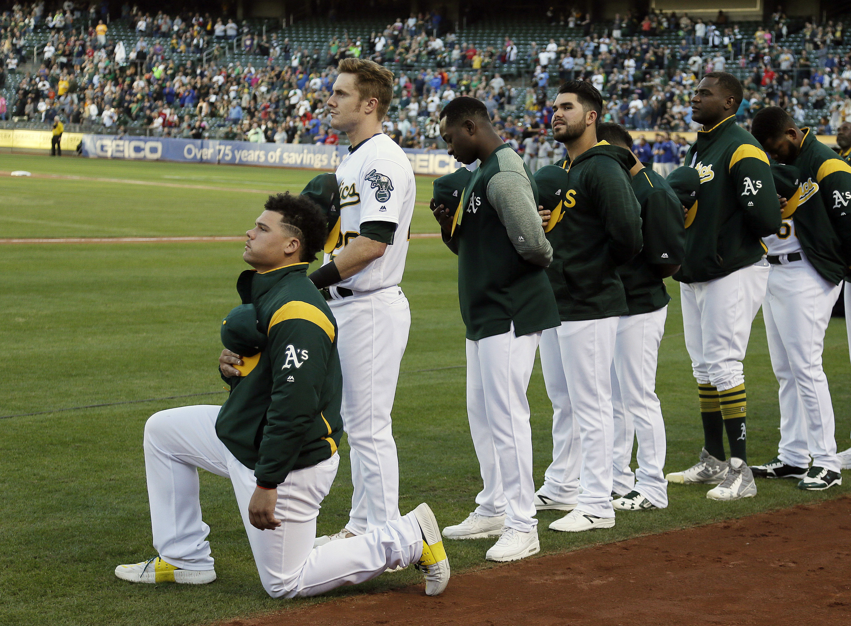 Oakland Athletics catcher Bruce Maxwell kneels during the national anthem Saturday in Oakland. Maxwell is the first Major League Baseball player to kneel during the national anthem. (Eric Risberg/AP)