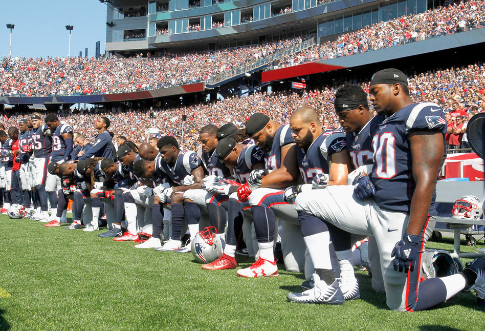 Members of the New England Patriots — and players across the league — kneel during the national anthem before Sunday's game against the Houston Texans. (Jim Rogash/Getty Images)