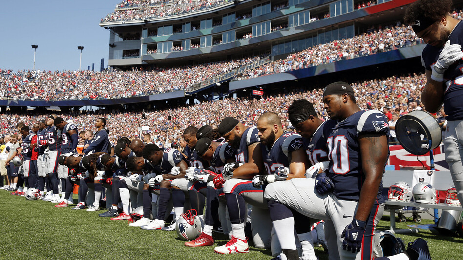 Several New England Patriots players kneel during the national anthem before an NFL football game against the Houston Texans. (Michael Dwyer/AP)