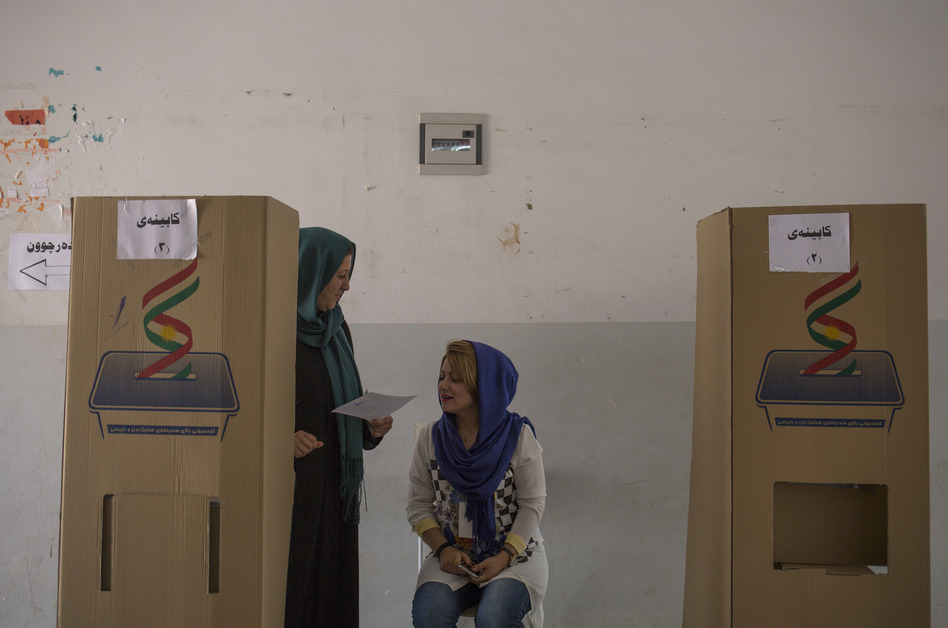 A volunteer looks at a voter's ballot as she walks out of a voting booth on Monday in the disputed city of Kirkuk, Iraq. (Bram Janssen/AP)