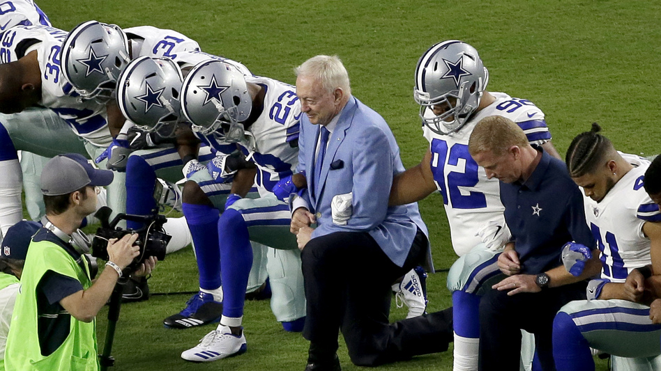 The Dallas Cowboys, led by owner Jerry Jones (center), take a knee before the national anthem Monday night in Glendale, Ariz., ahead of the team's game against the Arizona Cardinals. (Matt York/AP)