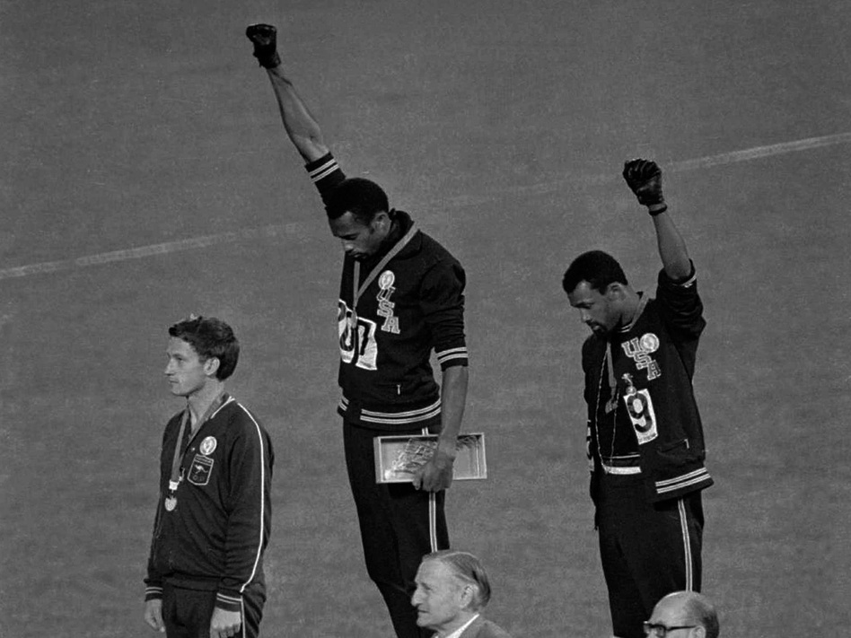 American gold medalist Tommie Smith (center) and bronze medalist John Carlos raise their fists in the air in a black power salute during the playing of the U.S. national anthem at the 1968 Olympics.