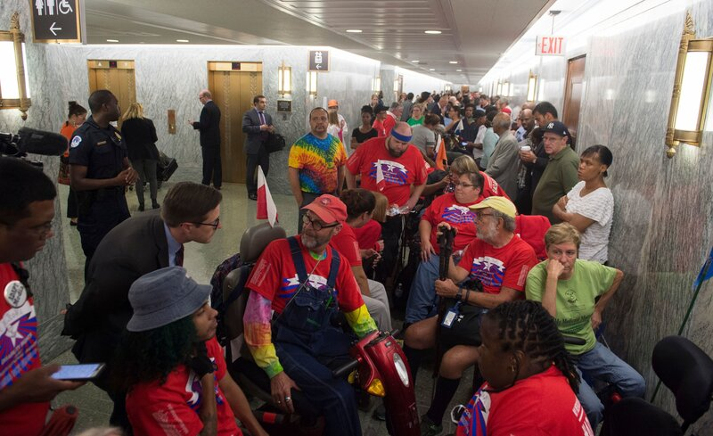 Activists and members of the public wait for a Senate Committee on Finance hearing on the latest GOP health care proposal on Capitol Hill on Monday. Once inside the hearing, activists began chanting and temporarily suspended the hearing. (Saul Loeb/AFP/Getty Images)