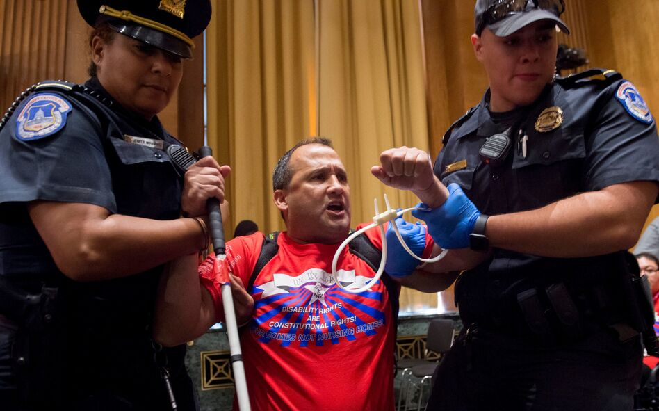 U.S. Capitol Police remove a protester from Monday's Senate Finance Committee hearing on the Graham-Cassidy health care plan to repeal Obamacare. (Saul Loeb/AFP/Getty Images)