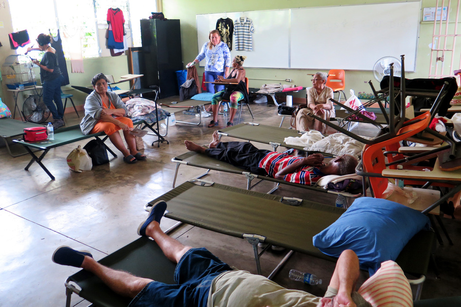 Carmen Rivera (at left in the orange dress) sits on a cot at the Cataño shelter. She suffers from severe asthma and knee pain and has had to be rushed by ambulance to the hospital for asthma treatment twice since the hurricane. She says she feels forgotten by authorities. (Greg Allen/NPR)