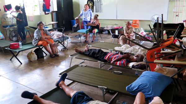 Carmen Rivera, at left in the orange dress, sits on a cot at the Cataño shelter. She suffers from severe asthma and knee pain and has had to be rushed by ambulance to the hospital for asthma treatment twice since the hurricane. She says she feels forgotten by authorities.