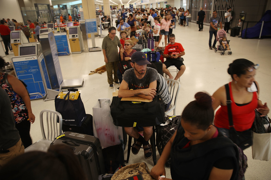 Edgar Algarin (center) and others wait in line to get a flight at the Luis Muñoz Marín International Airport in San Juan, Puerto Rico, on Monday. Hurricane Maria has left the island without power and with dwindling supplies of food and fuel. (Joe Raedle/Getty Images)