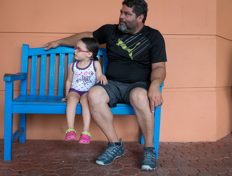 Angelica Alicea, 3, and her grandfather Julio Alicea wait outside the San Jorge Children's Hospital. (Angel Valentin for NPR)
