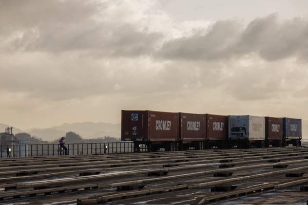 Crowley shipping containers are unloaded from a barge in the port of San Juan. The company started unloading shipments on Saturday. By Friday, it will have received four ships, with a total of about 4,000 loaded crates.