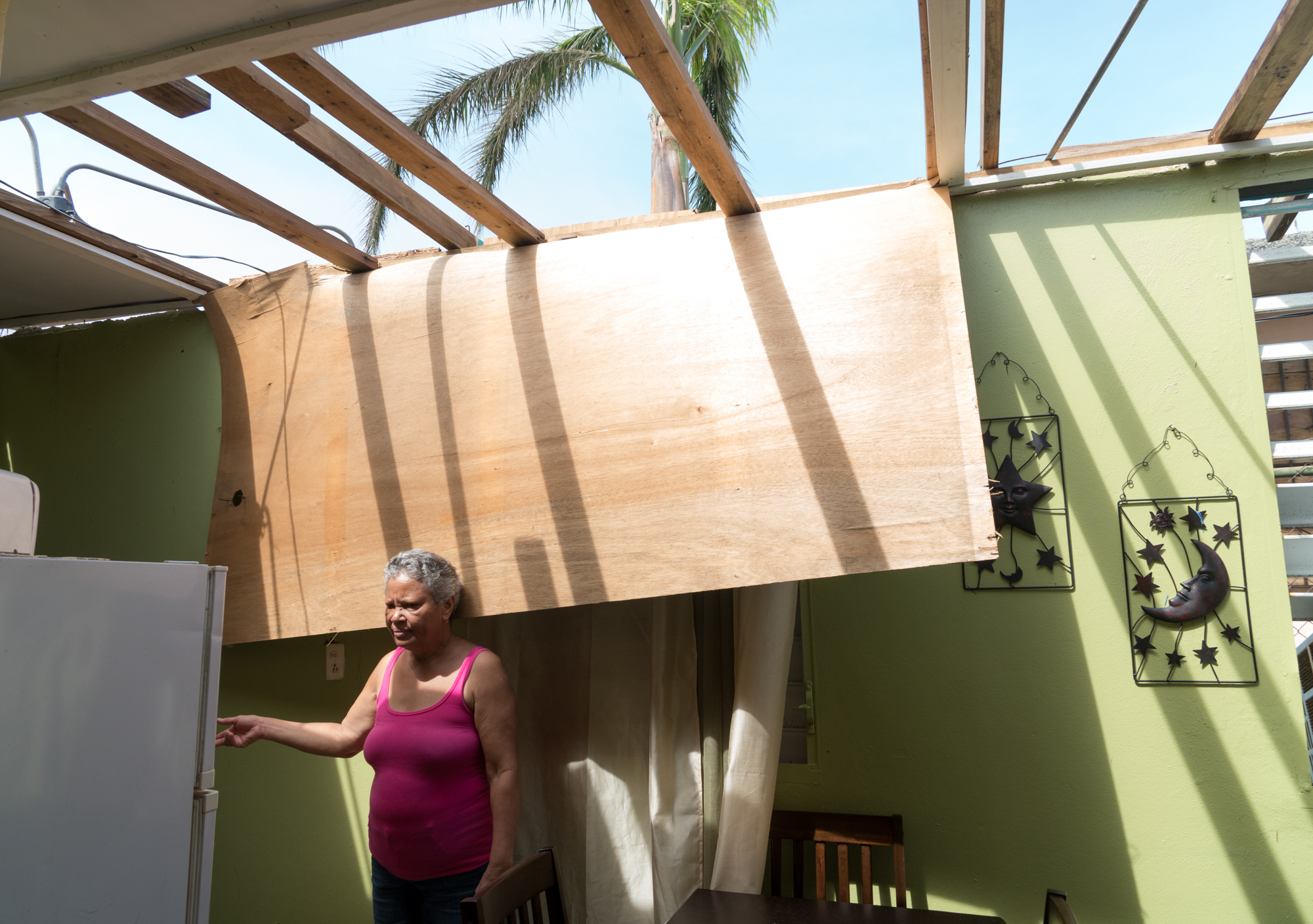 Maria Reyes, 63, stands in her home, which was severely damaged by the storm. She spends most of her time these days caring for her 82-year-old mother, Rafaela. (Angel Valentin for NPR)