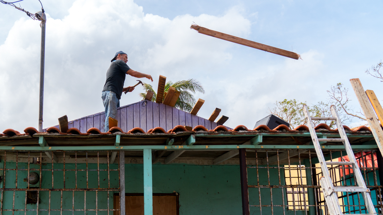 A man's works on his house, which was severely damaged by Hurricane Maria, in San Juan's Playita neighborhood in Puerto Rico. Infrastructure problems that predated the hurricane dramatically worsened the situation in Playita. (Angel Valentin for NPR)