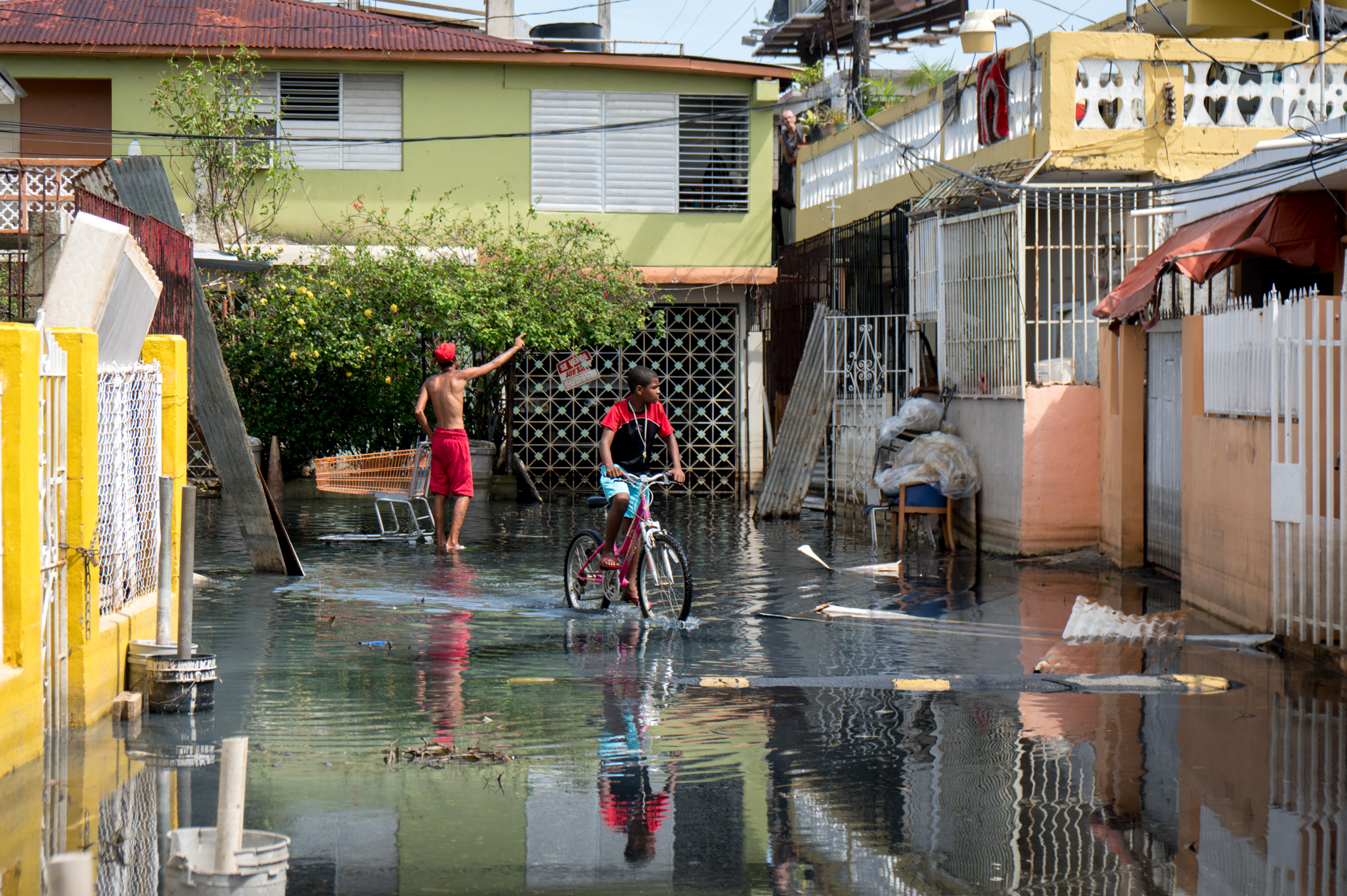 Children walk through standing flood water in the Playita neighborhood. There are small signs that the situation here is improving – but for the residents living through it, the progress is painfully slow. (Angel Valentin for NPR)