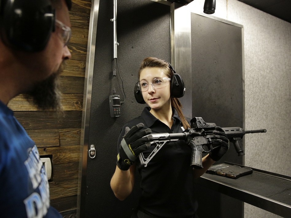 Shayna Zerbe, right, instructs Garret Sloan on how to fire a fully automatic machine gun in 2014 at Machine Guns Vegas. Nevada's gun laws are lax compared to other states, and gun tourism is nearly as ubiquitous in Las Vegas as gambling and stage shows.