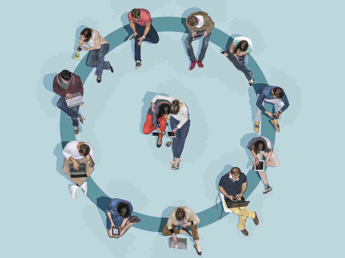 Group of young people using technologies sitting on a blue circle